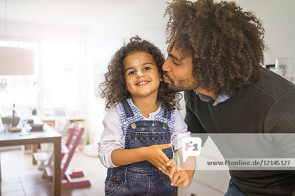 Vater küsst schmutzige Tochter in der Küche