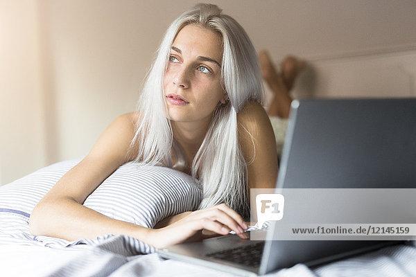 Junge Frau im Bett liegend mit Laptop