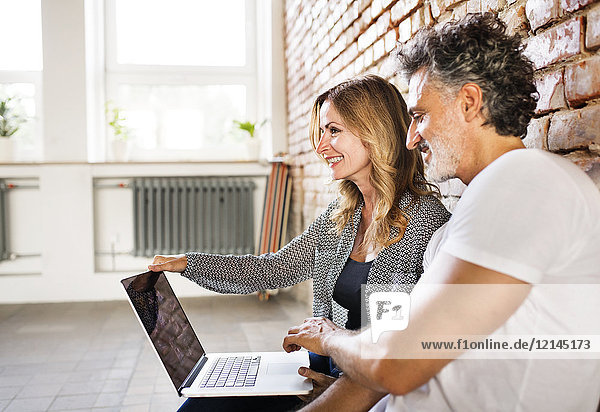 Businessman and woman sitting in a loft  using laptop  founding a start-up company