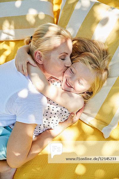 Glückliches Mädchen und Mutter umarmend und küssend auf einer Decke