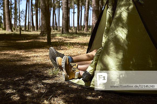 Schuhe ragen aus einem Zelt im Wald.