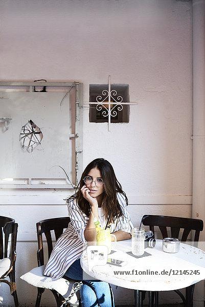 Porträt einer jungen Frau  die in einem Coffee Shop sitzt