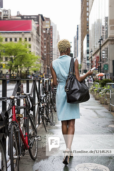 USA  New York  young blonde african-american woman with smart phone walking on walkway