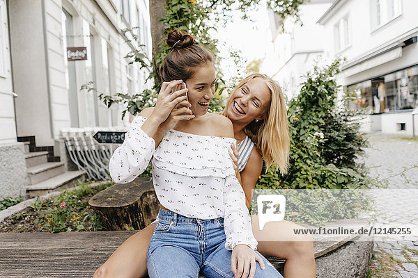 Two happy young women with cell phone in the city
