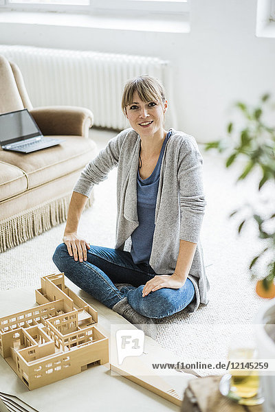 Portrait of smiling woman in office with architectural model