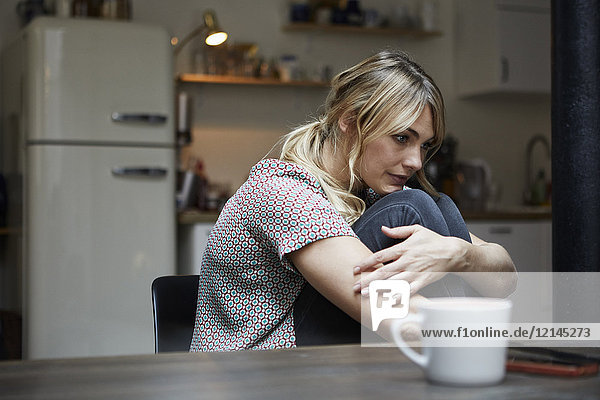 Porträt einer nachdenklichen Frau  die am Tisch in der Küche sitzt.