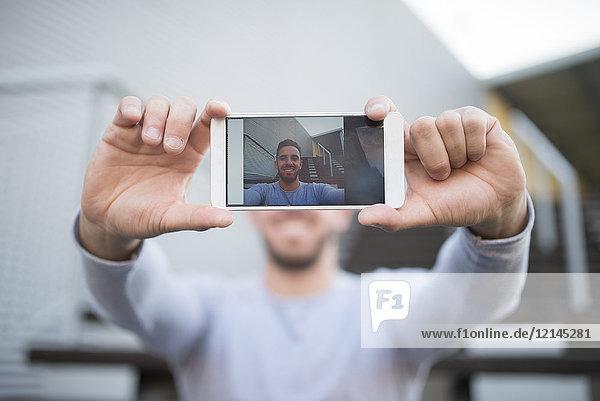 Lächelnder Mann nimmt Selfie mit Handy  Nahaufnahme