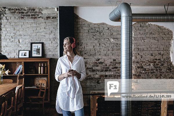 Junge Frau steht im Café  trägt Kopfhörer  benutzt Smartphone
