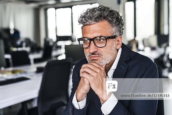 Porträt eines seriösen reifen Geschäftsmannes mit Brille im Büro