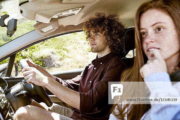 Junger Mann mit Freundin beim Autofahren
