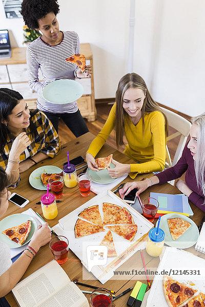 Gruppe junger Frauen zu Hause beim Lernen und Pizza essen