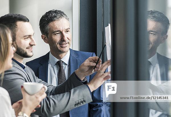 Lächelnde Geschäftsleute reden im Büro am Fenster