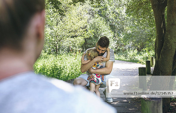 Little girl hugging her father on a wooden walkway in the countryside
