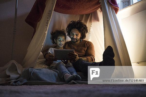 Vater und Tochter sitzen im dunklen Kinderzimmer und sehen sich das digitale Tablett an.