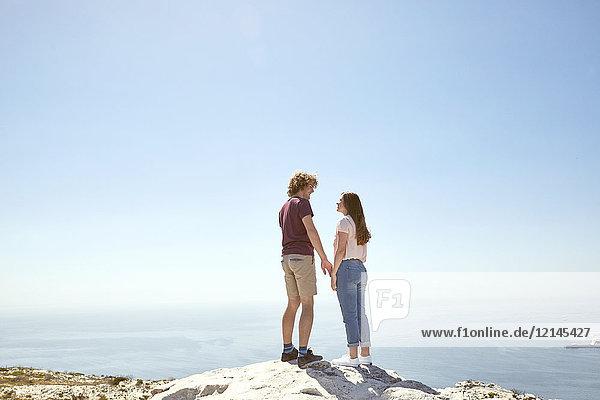 Südafrika  Kapstadt  junges Paar auf einem Berg an der Küste stehend