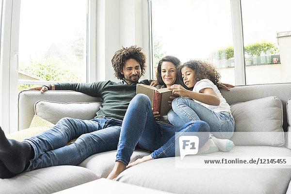 Glückliche Familie sitzend auf der Couch  Lesebuch