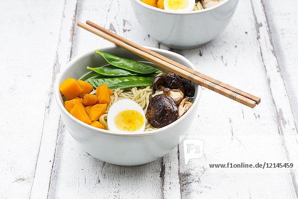 Ramen with noodles  egg  hokkaido pumpkin  mung sprout  shitake mushroom in bowl  chopsticks