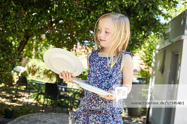 Blondes Mädchen hält Teller im Garten