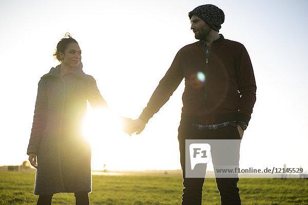 Zärtliches junges Paar  das bei Sonnenuntergang Hand in Hand auf einer Wiese steht.
