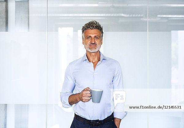 Porträt eines selbstbewussten Geschäftsmannes mit Kaffeetasse