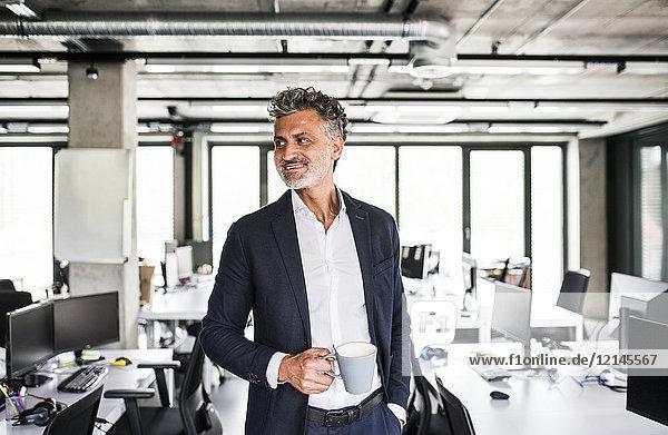 Lächelnder reifer Geschäftsmann mit Kaffeetasse im Büro