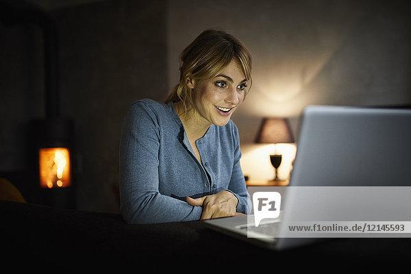 Porträt einer verblüfften Frau  die abends zu Hause mit dem Laptop unterwegs ist.