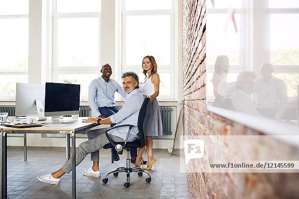 Porträt der lächelnden Kollegen am Schreibtisch im Loftbüro