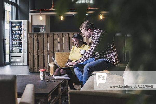 Kollegen arbeiten zusammen am Laptop in einem Cafe