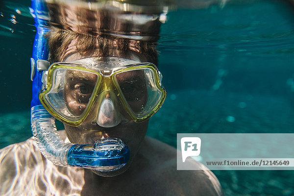 Porträt eines Mannes mit Taucherbrille und Schnorchel unter Wasser im Schwimmbad
