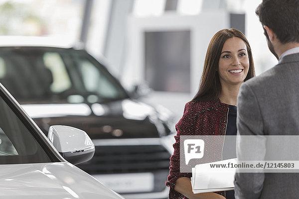 Lächelnde Kundin hört dem Autoverkäufer im Autohaus zu