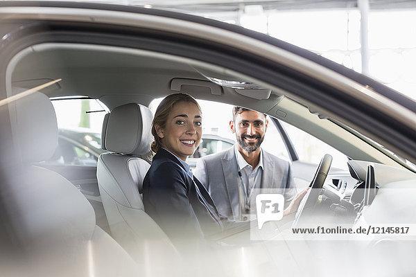 Porträt einer lächelnden Frau und eines Autoverkäufers im Neuwagen im Autohaus