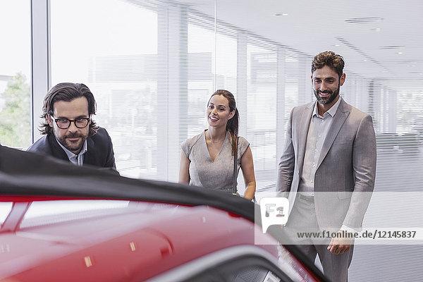Autoverkäufer zeigt Neuwagen  um Kunden im Autohaus zu verkuppeln