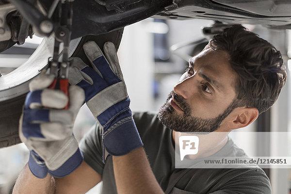 Fokussiertes männliches mechanisches Befestigungsrad unter dem Auto in der Werkstatt