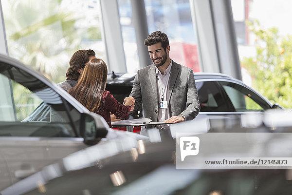 Autoverkäufer beim Händeschütteln mit Kunden im Autohaus-Showroom