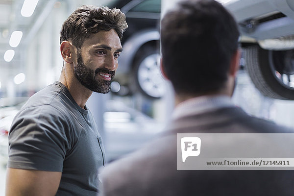 Smiling male auto mechanic talking to customer in auto repair shop