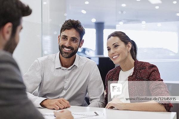 Lächelndes Paar Kunden im Gespräch mit Autoverkäufer im Autohausbüro
