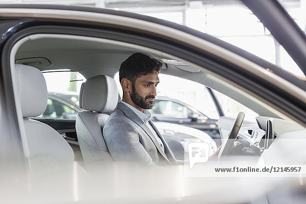 Männlicher Kunde sitzt auf dem Fahrersitz eines Neuwagens im Autohaus.