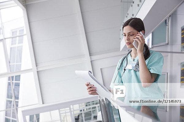 Krankenschwester mit Klemmbrett am Handy im Krankenhaus