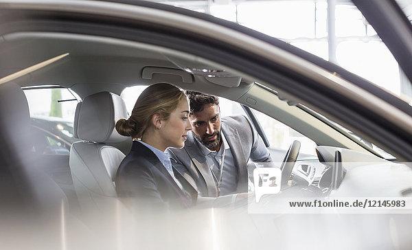 Autoverkäufer zeigt Neuwagen der Frau auf dem Fahrersitz im Autohaus