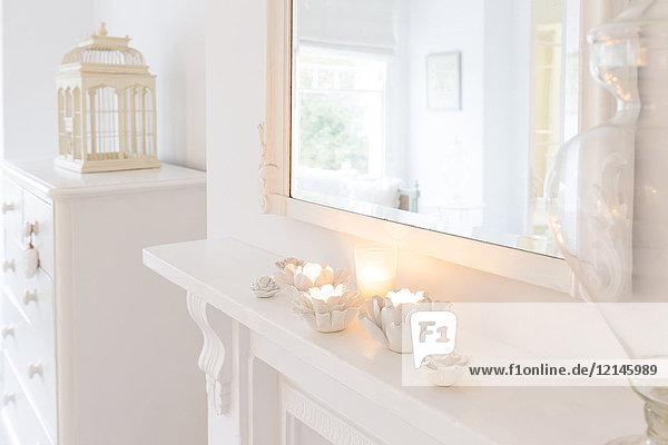 Ruhige Kerzen in Blumenkerzenhaltern auf weißem Mantel