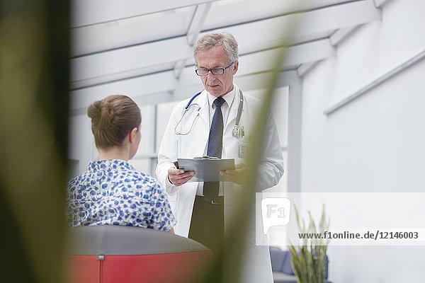 Männlicher Arzt mit Klemmbrett im Gespräch mit Patientin in der Lobby des Krankenhauses