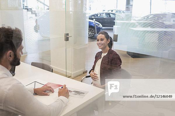 Autoverkäufer im Gespräch mit schwangeren Kunden im Autohausbüro