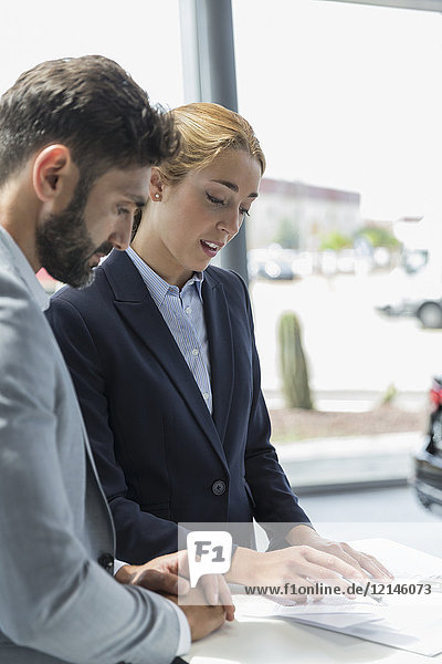 Car saleswoman explaining financial contract paperwork in car dealership