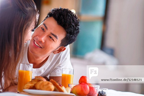 Young couples have breakfast in bed