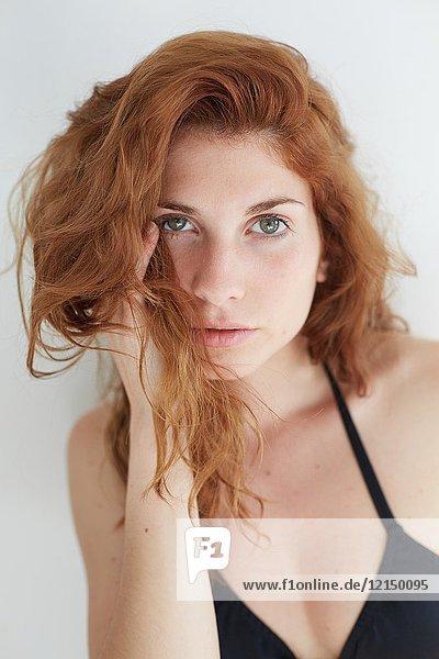 Half length portrait of young redhead woman wearing a black bikini  looking at camera