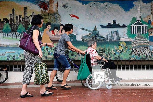 Woman pushing older woman in wheelchair.