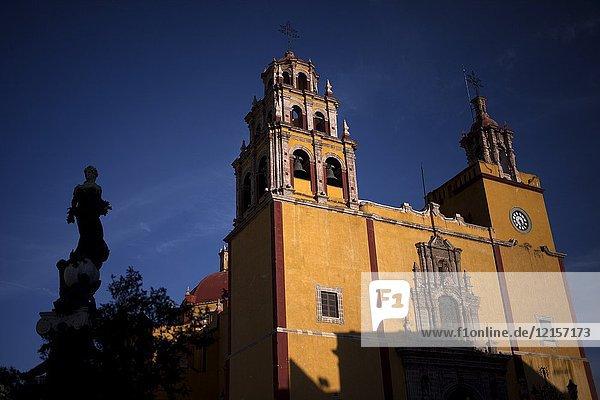 The Basilica of Our Lady of Guanajuato in Guanajuato and the silhouette of the Monumento a la Paz (Peace monument) in Guanajato  Mexico.