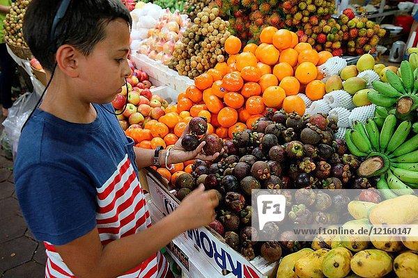 10-year-old European boy buying fruit in Cambodia.