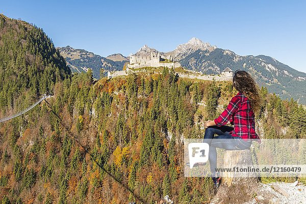 Reutte  Tyrol  Austria  Europe. Ehrenberg Castle and the Highline 179  the world's longest pedestrian suspension bridge. A young woman admiring the view.
