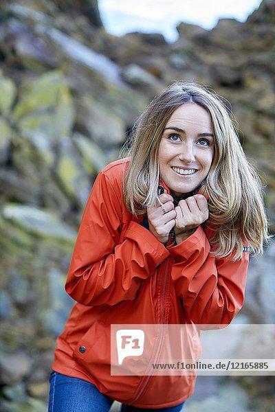Adult woman at the coast of Santa Clara Island  Donostia  San Sebastian  Gipuzkoa  Basque Country  Spain  Europe  Raincoat  Winter